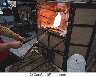 Glass blowing process. Artist prepare melted glass on blowing pipe