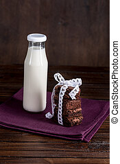 glass bottle of milk with brownie cakes with white ribbon on napkin at tabletop