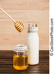 glass bottle of milk with honey in jar on wooden background