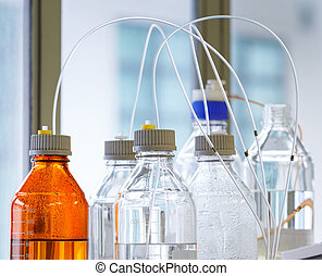 Glass bottle with plastic hose - Close up clear and amber...