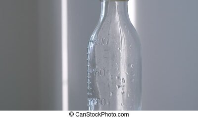 Glass bottle with water and teat in maternity hospital -...