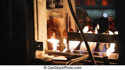 Glass bottles move along conveyor line fall under open flame...