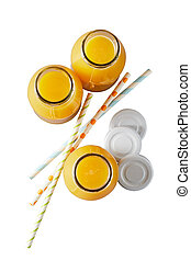 Three recyclable glass bottles of freshly squeezed orange juice rich in vitamin C viewed top down with lids and straws isolated on white