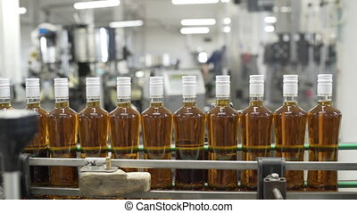 Glass bottles sealed with white foil and filled with alcohol move along conveyor line with control panel in Factory for bottling alcoholic beverages. Production process of prune tincture.