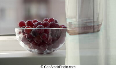 Glass bowl bunch of red grapes on windowsill of open apartment window closeup