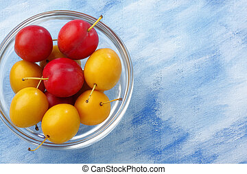 Glass bowl filled by yellow and red mirabelle plums over...