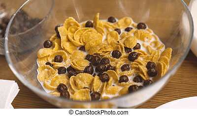 Glass bowl of Cornflakes with chocolate balls and milk on a wooden table. Cereal breakfast. Healthy quick food concept. Close up