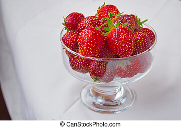 Glass bowl of fresh ripe strawberries on the tablecloth
