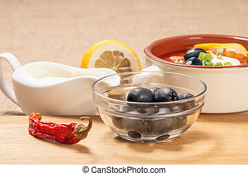 Glass bowl with black olives, dried red pepper on cutting board and ceramic soup bowl with saltwort, sauceboat and cut lemon.