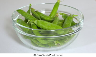 Glass bowl with fresh raw green pea pods on the table closeup