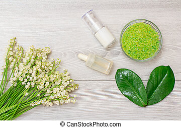 Glass bowl with sea salt, bottles with cream for face skin and aromatic oil, green leaves and bouquet of lilies of the valley.