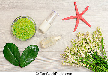 Glass bowl with sea salt, bottles with cream for face skin and aromatic oil, green leaves and bouquet of lilies of the valley