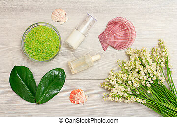 Glass bowl with sea salt, green leaves, bottles with cream for face skin and aromatic oil, sea shells and bouquet of lilies of the valley