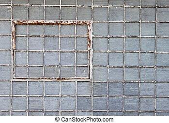 Glass brick wall with a rusty window