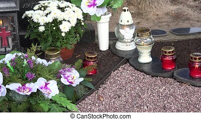 Glass candle lamp and chrysanthemum flowers on gravestone. ...