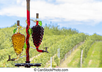 glass carafe with white and red wine in the shape of a grape and vineyard background