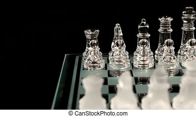 Glass chess board on black background. Crane shot. Chess...