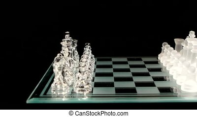 Glass chess board with figures on black background. Cam...