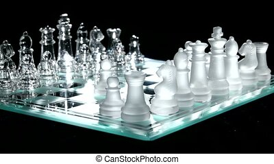 Glass chess on chesboard. Black background. Rotation cam