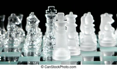 Glass chess on chessboard isolated on black