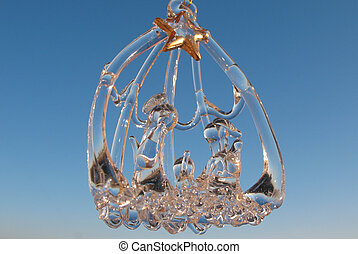 Glass Christmas-tree decorations «Holy Family» on the background of blue sky