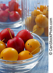 Glass containers filled by yellow and red mirabelle plums -...