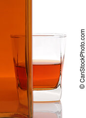Glass cup and bottle of whiskey