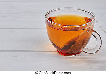 Glass cup of black tea on wooden background.