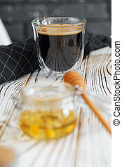 Glass cup of coffee on wooden kitchen table