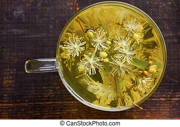 Glass cup of linden tea with fresh flowers