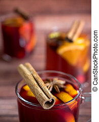 Glass Cup of red wine mulled wine on a wooden background with cinnamon spices and orange. Selective focus