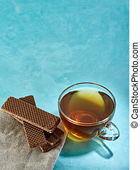 Glass cup of tea and waffles close-up on blue background, vertical