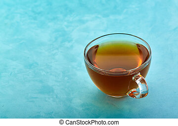 Glass cup of tea close-up on blue background.