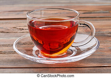 Glass cup of tea on wooden background.