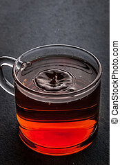 Glass cup of tea with falling drop