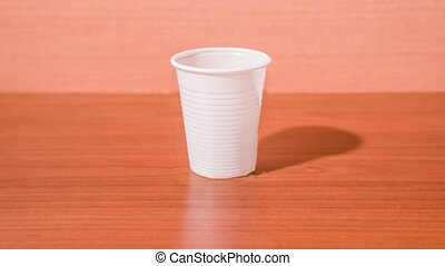 Glass cup turns into plastic cup on the wooden table