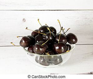 Glass cup with maroon cherries on a light wooden background