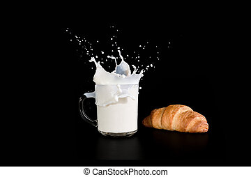 Glass cup with milk and croissant on a dark background