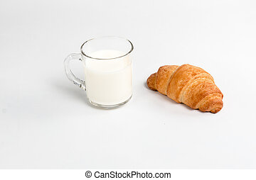 Glass cup with milk and croissant