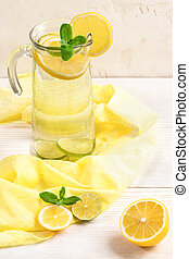 Glass decanter with water, infused with lemon and lime, on yellow cloth on light wooden table.