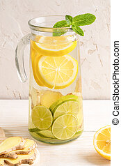 Glass decanter with water, infused with lemon, lime and ginger on light background.