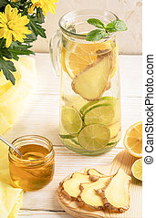 Glass decanter with water, infused with lemon, lime, ginger and ingredients on light background.