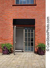 glass door in brick wall with two flowerpots
