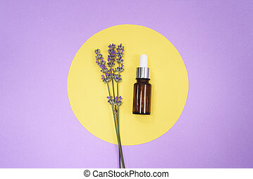 Glass dropper bottle and lavender on yellow circle on purple background.