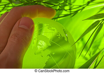 Glass earth in grass with hand