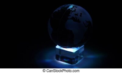 Glass Earth sphere rotates on cube with color illumination