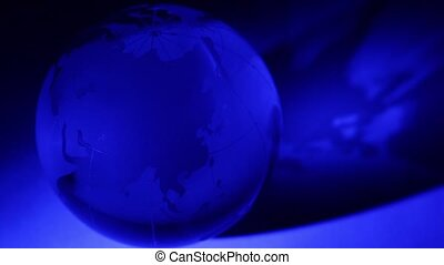 Glass Earth sphere spins with blue color illumination at...