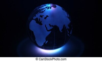Glass Earth sphere with color illumination at dark...