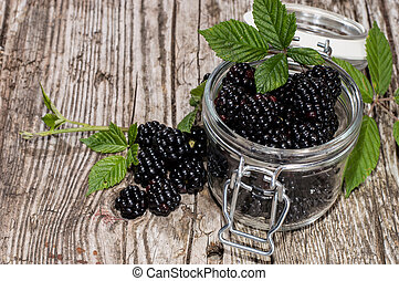 Glass filled with fresh Blackberries on wooden background