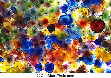 Multi-colored glass flowers that are backlit.